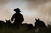 Horseback riding at dusk, in a Utah field.