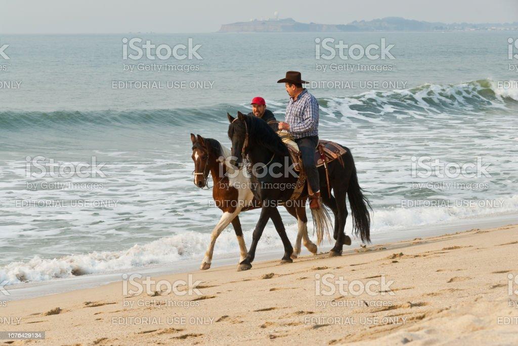 Horseback Riding at the Pacific Ocean stock photo
