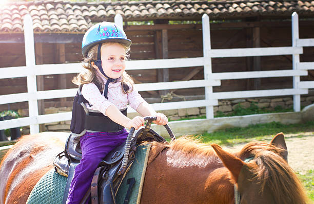 Horseback riding lesson Little girl holding on to the saddle during riding lesson. alternative therapy stock pictures, royalty-free photos & images