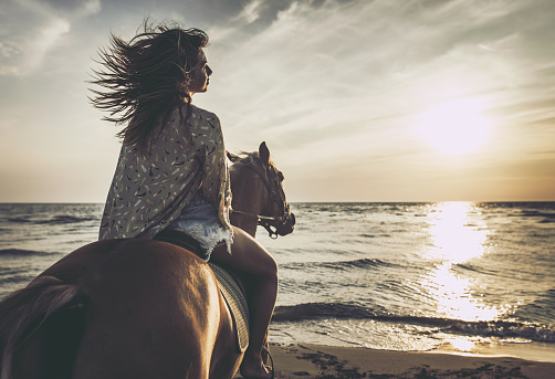 Back view of a woman riding a horse on the beach.
