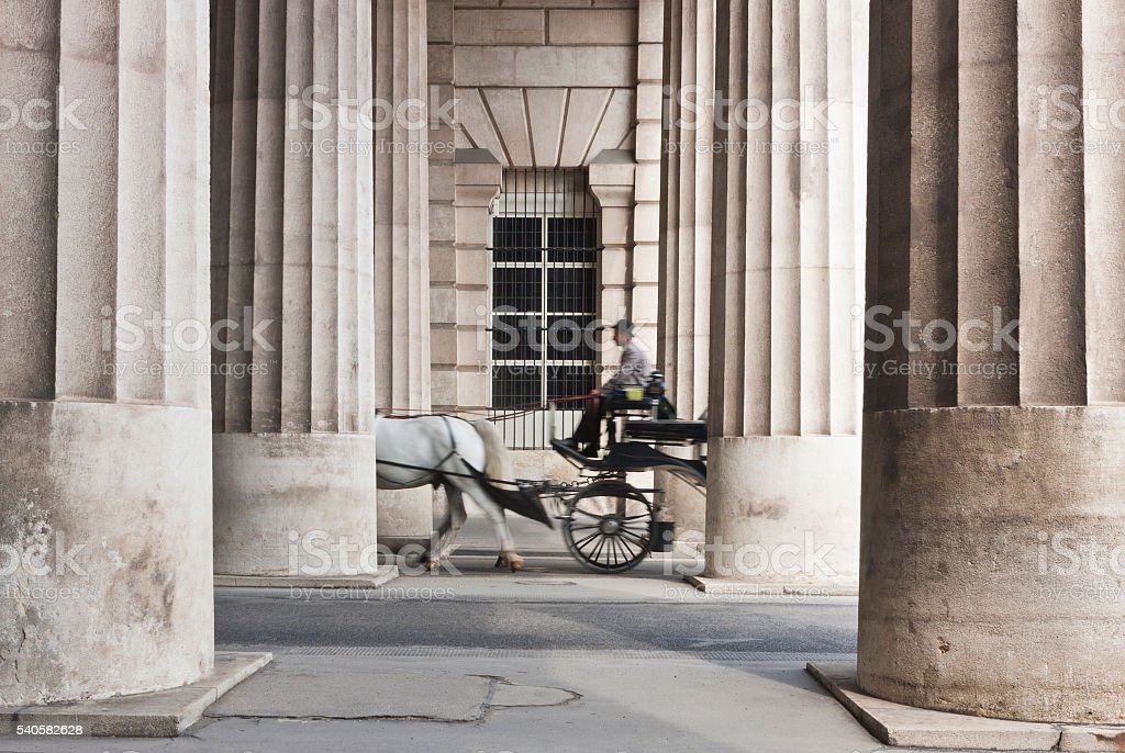 Horse-drawn carriage passing through the collonnade stock photo