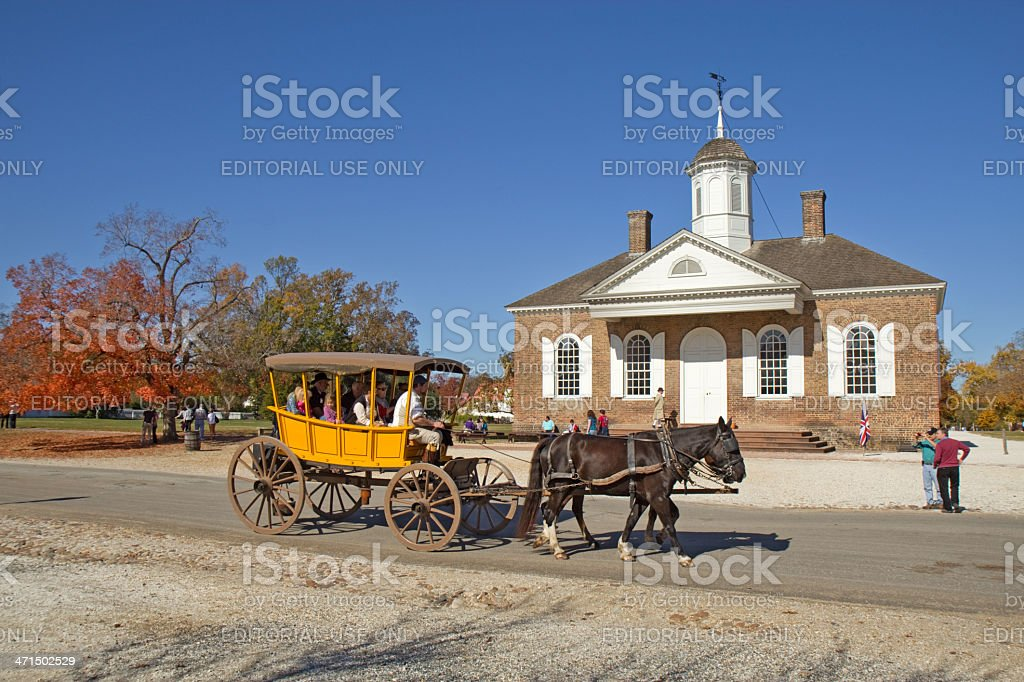 Horse-drawn carriage rides in front of the courthouse building royalty-free stock photo