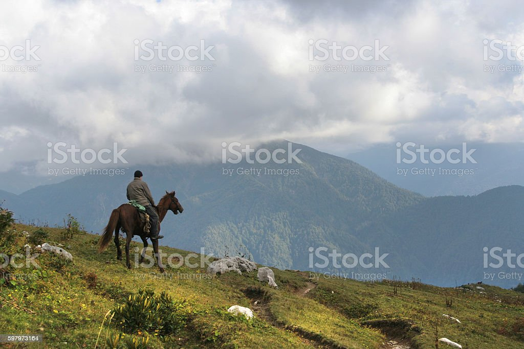 Horseman ride on top of mountains stock photo