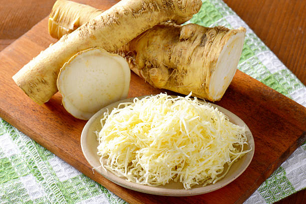 horseradish horseradish on wooden cutting board and dishtowel horseradish stock pictures, royalty-free photos & images