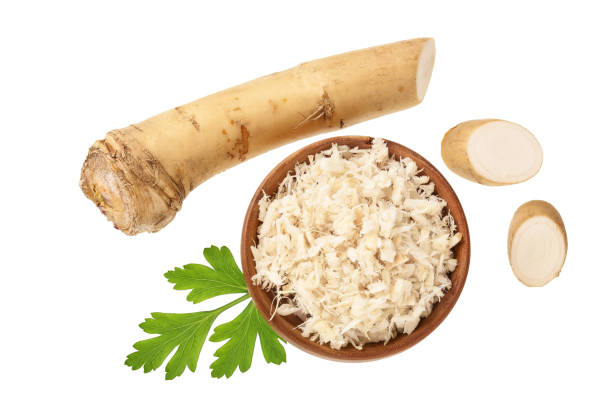 Horseradish root grated in wooden bowl with slices isolated on white background. Top view. Flat lay Horseradish root grated in wooden bowl with slices isolated on white background. Top view. Flat lay. horseradish stock pictures, royalty-free photos & images