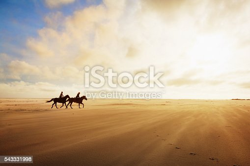 Two women ride horses across the sand on a winter's afternoon, silhouetted by golden sunlight which tints both sand and clouds. Ample copy space on clouds and sand.