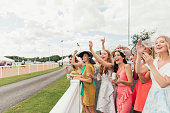 A group of young women cheering on the horses as they race by on the track at ladies day.