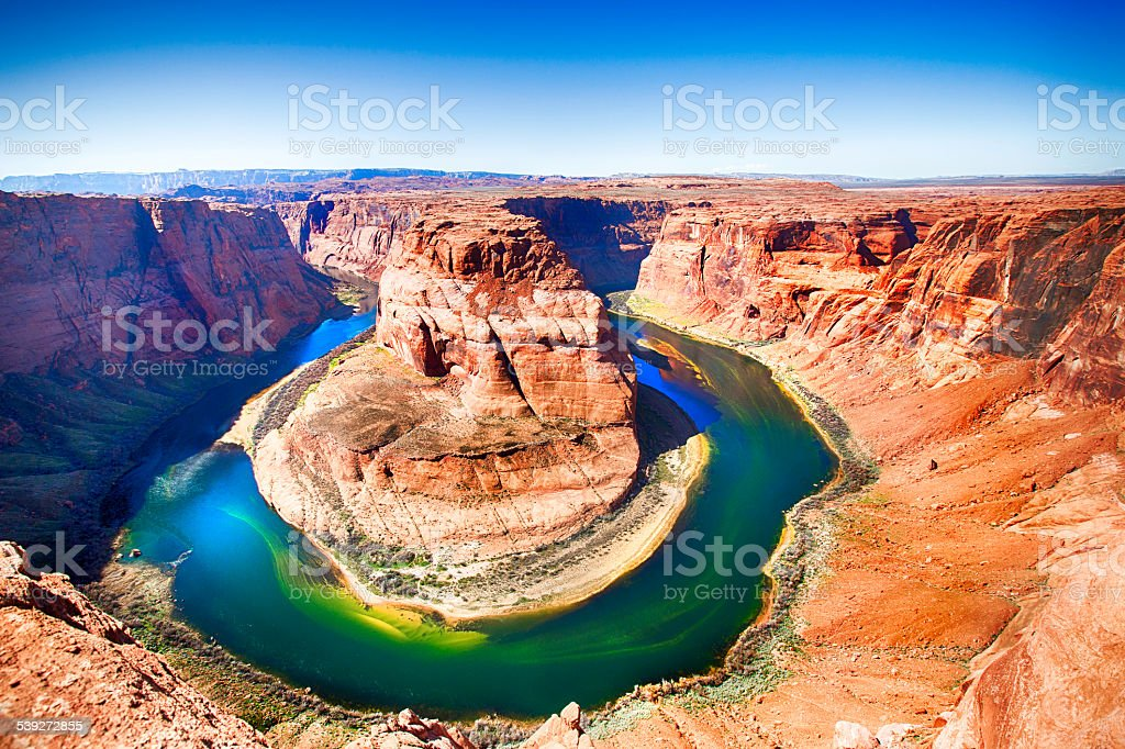 Horseshoe Bend Colorado River Horseshoe Bend at the Colorado River in hues of bright orange, greens, blues and yellows. This natural attraction is located in Page Arizona. Taken with a 5D mark 3 Camera. Arizona Stock Photo