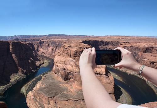 Horseshoe bend. Person taking photo of Colorado river at Horseshoe bend, Arizona USA.
