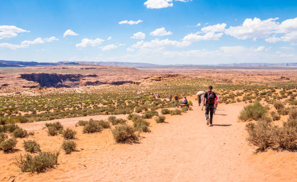 Horseshoe bend. Tour in Arizona. Tourists in the desert area of the Grand Canyon and the Colorado River. Page, Arizona, USA - June 20, 2017: Tourists walking along the dirt road to Horseshoe bend on the Colorado River in Arizona. Desert locality and tourist attractions of Arizona. Traveling on a summer vacation in the USA horseshoe bend colorado river stock pictures, royalty-free photos & images