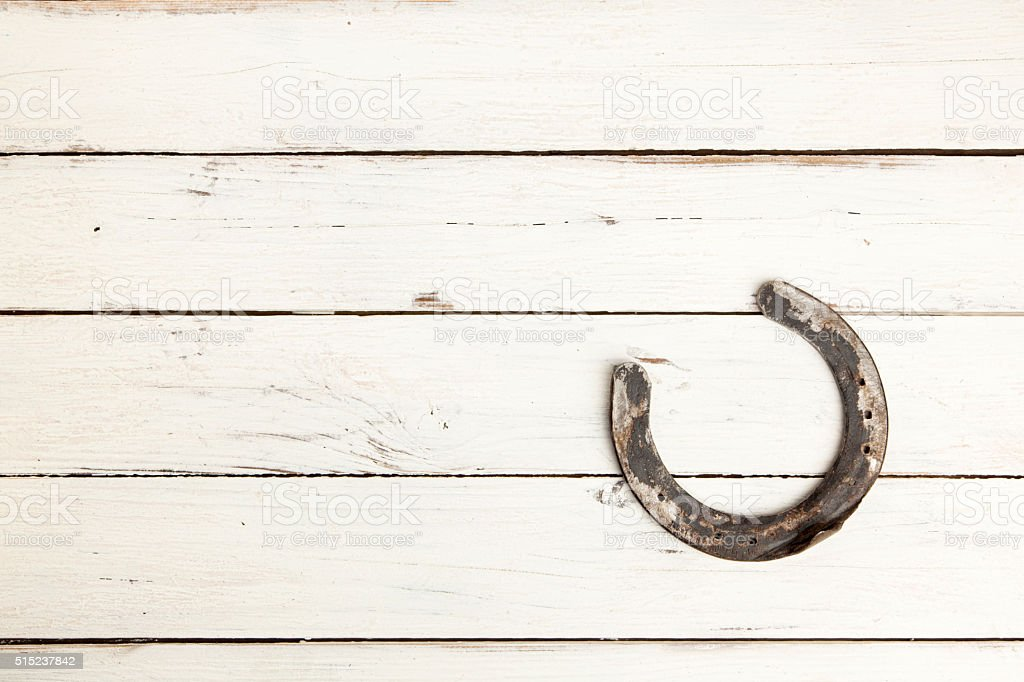 Horseshoe on white wooden background stock photo