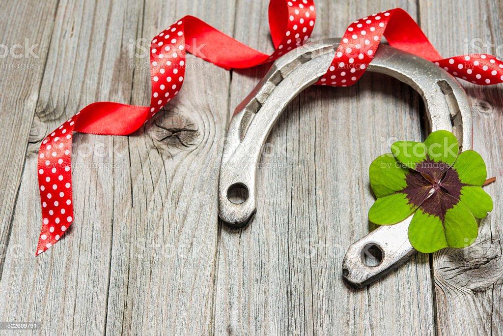 Horseshoe, shamrock and red ribbon on old wooden stock photo