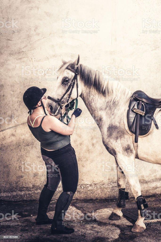 Horsewoman preparing her horse stock photo