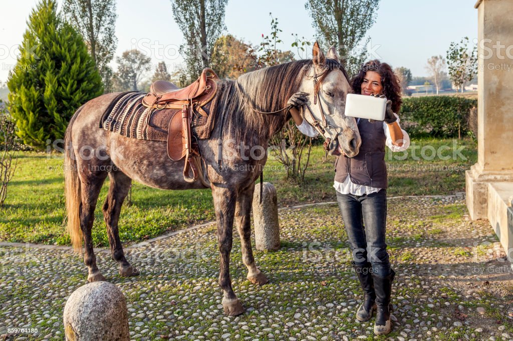 horsewoman takes a selfie with his horse stock photo