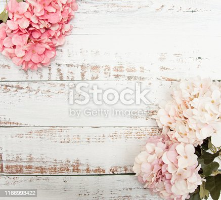 Hortensia flowers on a light wooden vintage background. Plastic flowers like real ones. Place for text.
