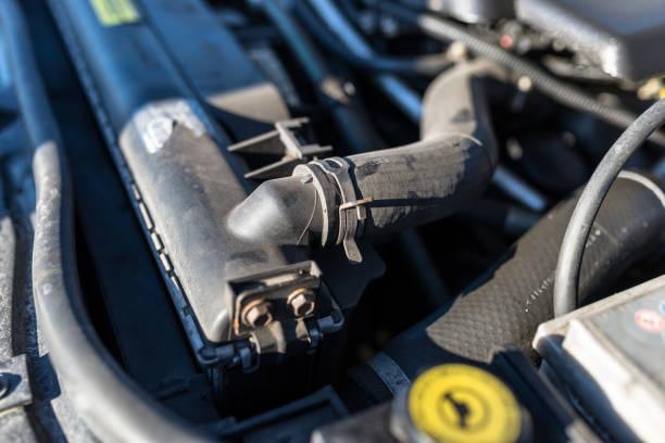 Schlauch, der den Kühler mit dem Motor verbindet, im Hintergrund der Motorraum. – Foto
