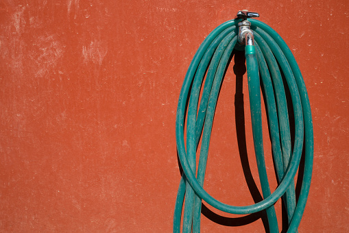 A hose hanged on a faucet on the colored wall