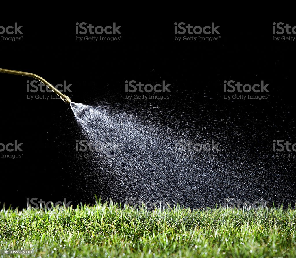 Hose watering grass on black background royalty-free stock photo