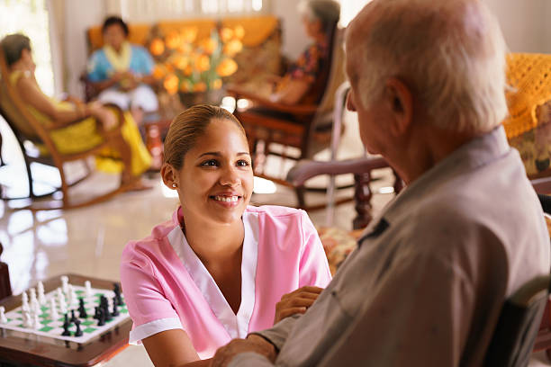 cuidados para enfermos terminales enfermera ayuda hombre de edad avanzada con acceso para silla de ruedas. - geriatría fotografías e imágenes de stock