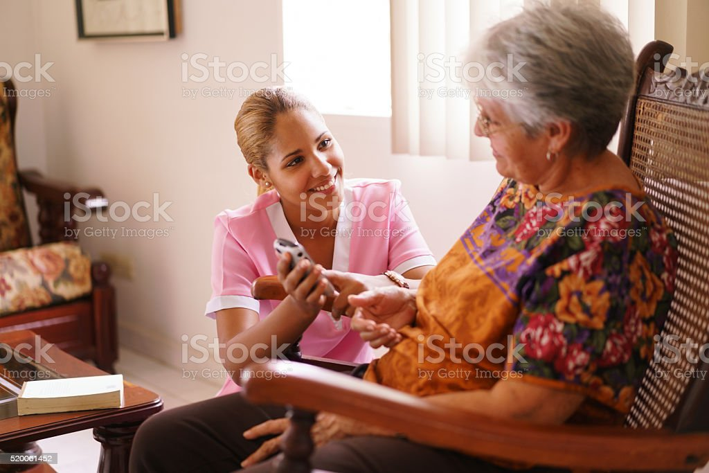 Hospice Nurse Helps Old Lady With Mobile Phone Call stock photo