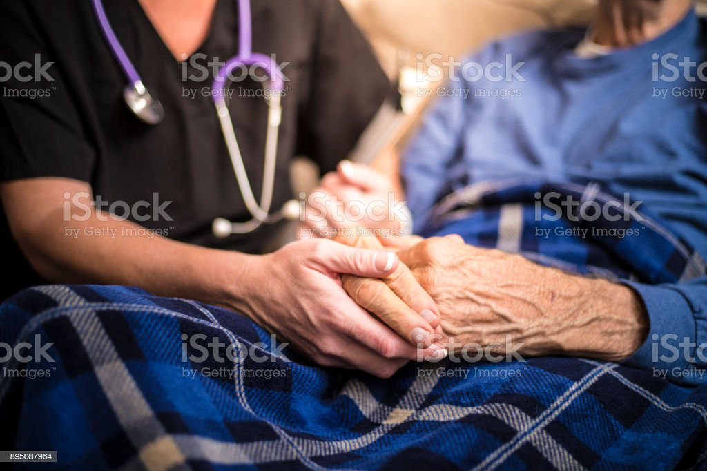 Hospice Nurse visiting an elderly male patient stock photo