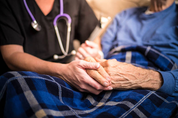 hospice nurse visiting an elderly male patient - accudire foto e immagini stock