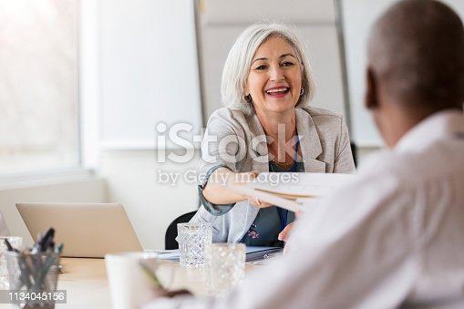 istock Hospital administrator hands document to doctor 1134045156