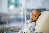 A young girl of African descent is indoors in a hospital room. She has cancer. She is lying in bed with her teddy bear while hooked up to an IV. She is looking at the camera.