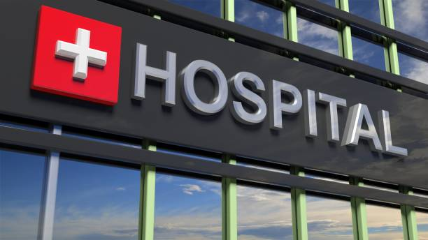 hospital building sign closeup, with sky reflecting in the glass. - hospital stock pictures, royalty-free photos & images