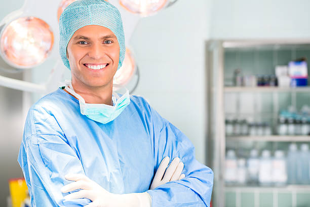 Hospital - doctor surgeon in operation theater Hospital - Young female doctor or surgeon in a sterile operating room, theater or clean room of a clinic anesthesiologist stock pictures, royalty-free photos & images