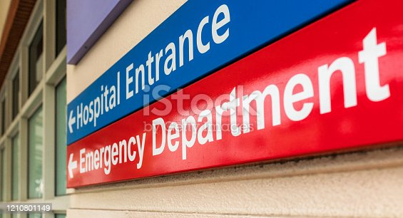 A hospital sign in London, giving directions towards the emergency department.