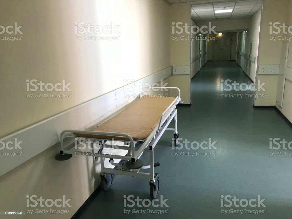 View of a long corridor with light walls in the hospital. There is a...