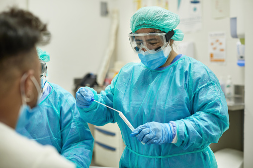 Over the shoulder view of healthcare worker in protective clothing, eyewear, bouffant cap, surgical mask, and gloves placing swab specimen in sterile container.
