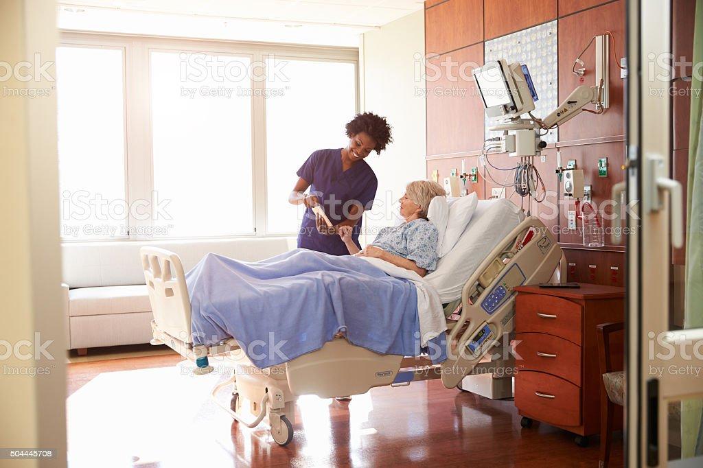 Hospital Nurse With Digital Tablet Talks To Senior Patient Stock Photo