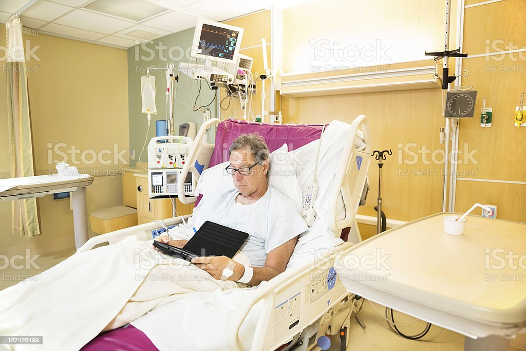 Hospital patient reading on a computer tablet royalty-free stock photo