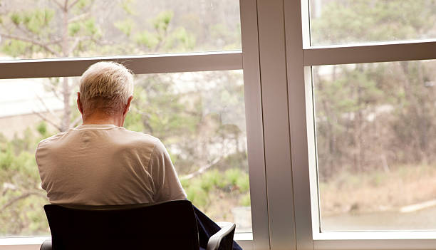 Hospital patient waiting by a window. Senior adult man. Depression. Patient in a hospital enjoying the view in a waiting room.  Senior adult man. one senior man only stock pictures, royalty-free photos & images