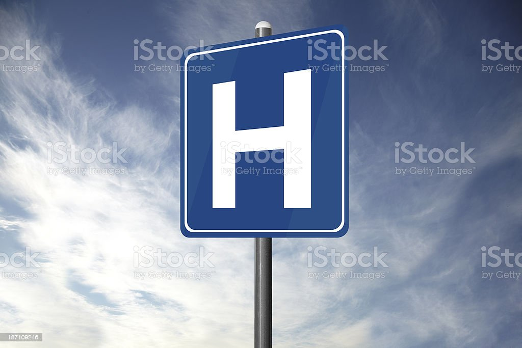 Hospital road sign standing alone with clouds overhead stock photo
