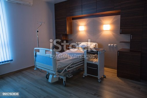 Empty hospital room for one client, evening light.