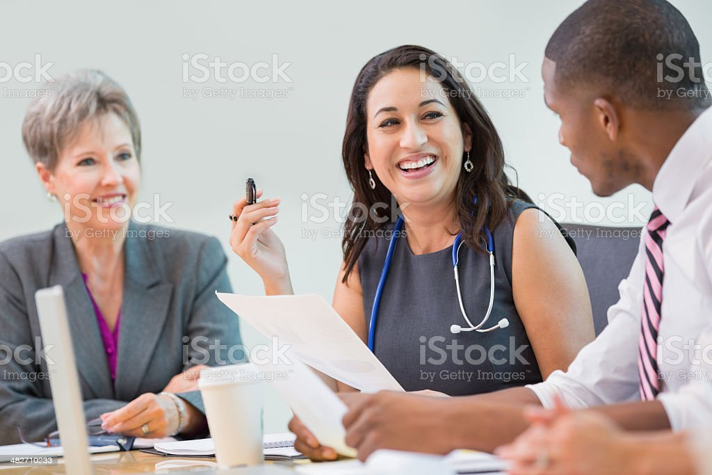 Hospital staff discussing healthcare procedures during board meeting stock photo