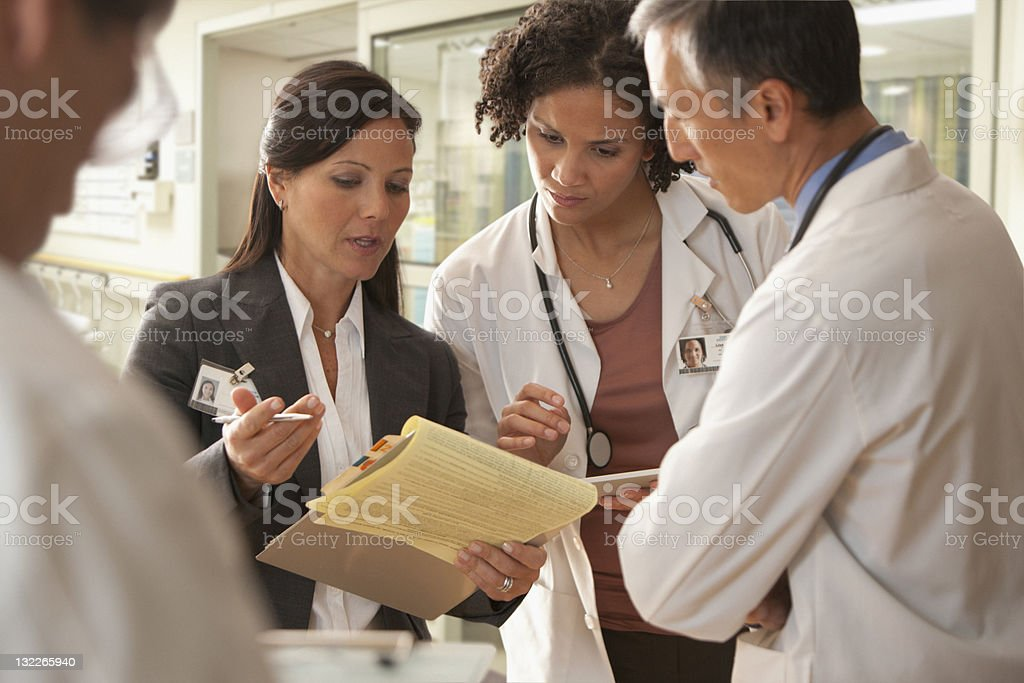 Hospital staff discussing patient charts stock photo