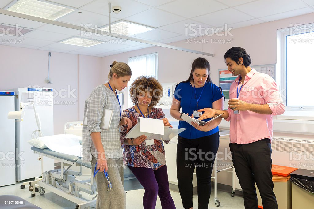 A group of young medical professionals are sitting in a doctors...