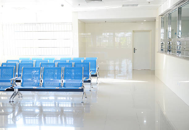 A hospital waiting room with blue chairs stock photo