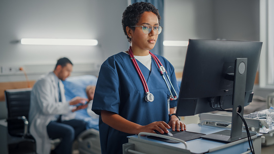 Hospital Ward: Professional Smiling Black Female Head Nurse or Doctor Wearing Stethoscope Uses Medical Computer. In the Background Patients in Beds Recovering Successfully after Sickness and Surgery