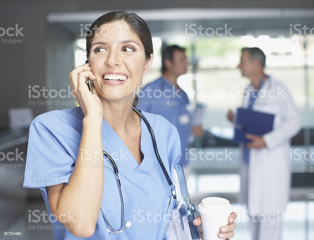 Hospital worker using cellular phone and smiling stock photo