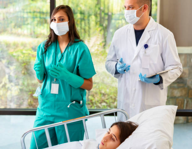 Hospital Workers Attending to Young Woman in Hospital stock photo