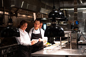 Chefs and restaurant manager discussing reservations. Foodservice and hospitality workers. Restaurant staff working.