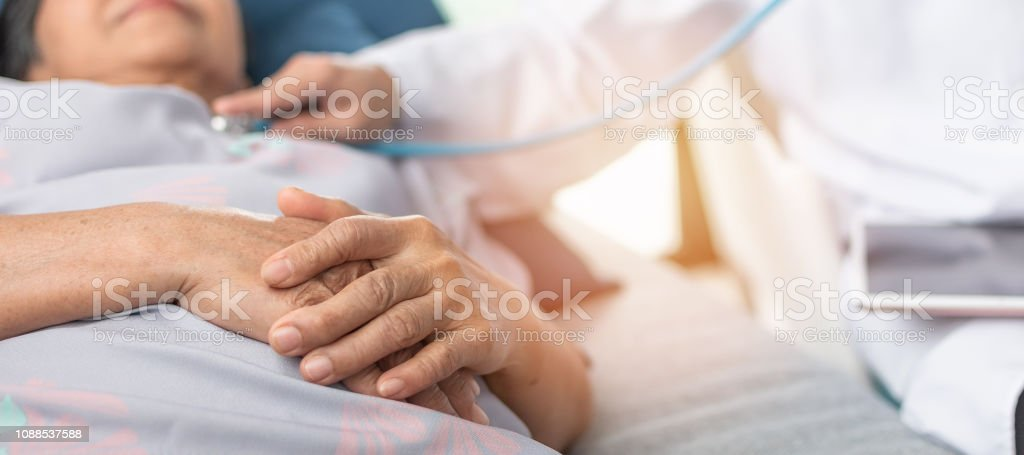 Hospitalized elderly patient, senior old aging woman laying on bed with cardiologist doctor or physician examining cardiological heart health, checking pulse in hospital clinic exam room Hospitalized elderly patient, senior old aging woman laying on bed with cardiologist doctor or physician examining cardiological heart health, checking pulse in hospital clinic exam room Adult Stock Photo