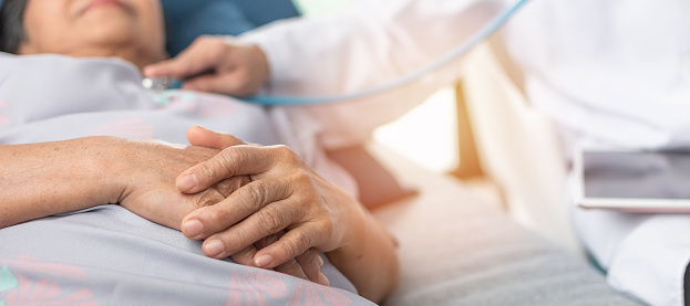 Hospitalized Elderly Patient Senior Old Aging Woman Laying On Bed With Cardiologist Doctor Or Physician Examining Cardiological Heart Health Checking Pulse In Hospital Clinic Exam Room Stock Photo - Download Image Now