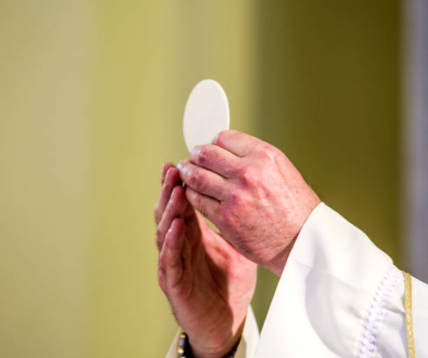 host that in the hands of the priest, as in the hands of Pope Francis, becomes the body of Christ stock photo