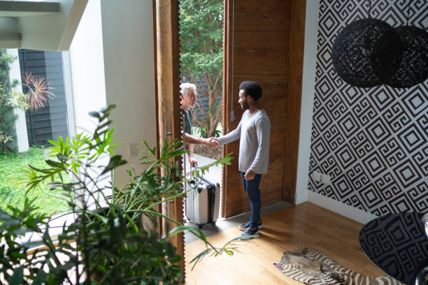 Host welcoming his guest in the entrance hall Host welcoming his guest in the entrance hall house rental stock pictures, royalty-free photos & images